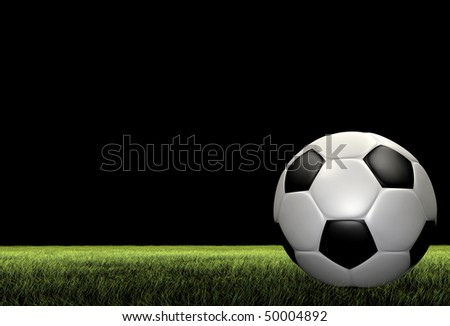 A render of a football soccer ball over grass on a black background - stock photo