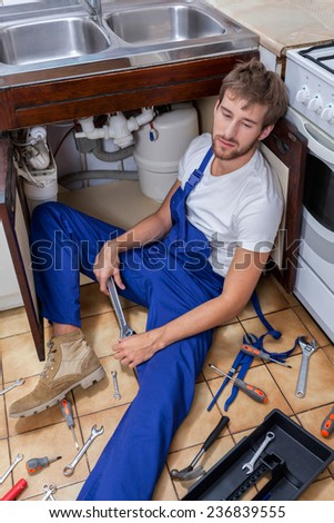A repair man bored with fixing a sink in a mess of tools