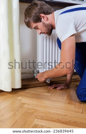 A repairman fixing a radiator in a flat