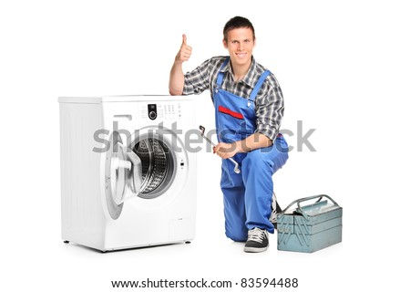 A repairman holding a spanner and giving thumb up next to a washing machine isolated on white background - stock photo
