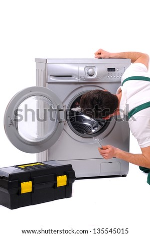 A repairman holding a spanner and posing next to a washing machine isolated on white background - stock photo