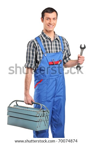 A repairman in blue overall holding a toolbox and wrench isolated on white background - stock photo