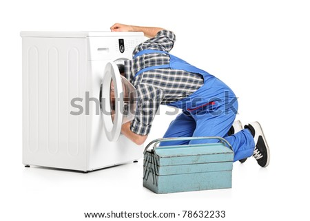 A repairman trying to fix a washing machine isolated on white background - stock photo