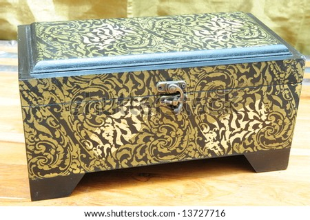 A replica of an antique jewelery box, made of wood with copper inlays.