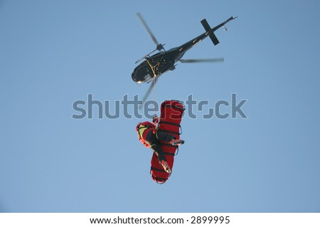 A rescue worker flies under a helicopter with a patient in a rescue stretcher. - stock photo