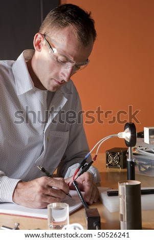 A researcher in a lab coat and goggles, making notes on an experiment. He is surrounded by scientific equipment. Vertical format. - stock photo