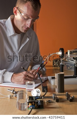 A researcher in a lab coat making notes on an experiment - stock photo