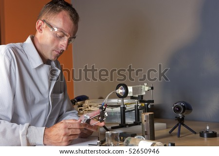 A researcher in a lab coat studying a piece of equipment for an experiment. He is wearing safety glasses. Horizontal shot. - stock photo