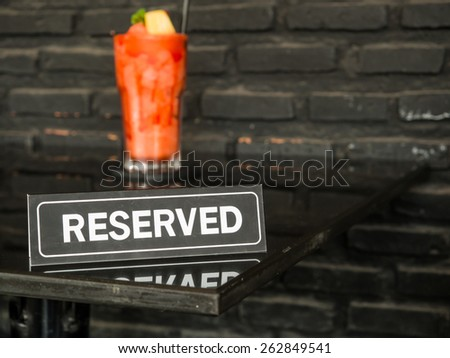 A reserved sign on a table with strawberry smoothies in restaurant. - stock photo