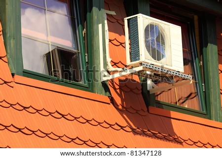 A residential central air conditioning unit hanging outside a home - stock photo
