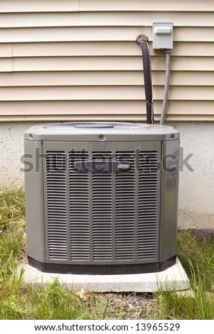 A residential central air conditioning unit sitting outside. - stock photo