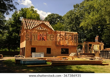 A residential home under construction mid framing and sheathing - stock photo