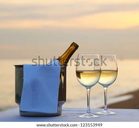 A restaurant table on a beach at sunset with two glasses of white wine and an ice bucket - stock photo