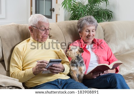 A retired couple relaxing is interrupted by their little  Brussels Griffon dog looking for attention. - stock photo