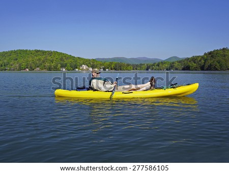 A retired gentleman resting in his kayak and enjoying the mountain lake. - stock photo