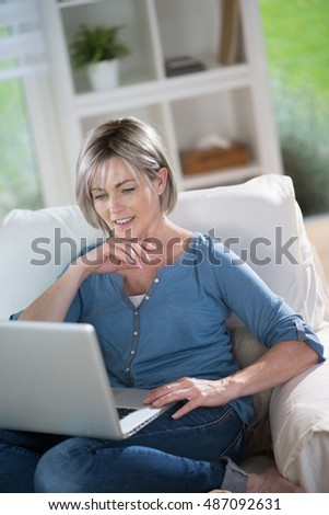 a retired woman with gray hair who browses the Internet with her laptop, she is sitting in a armchair. she  smiles. she is in her living room in the foreground