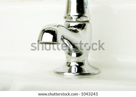 A retro bathroom sink tap detail. - stock photo