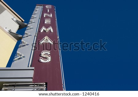 "A retro ""Cinemas� sign, outside of a movie theater."