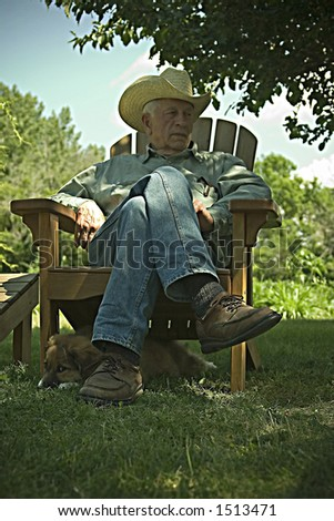 A retro photo of a puppy and a country gentleman relaxing in the shade on a hot day. - stock photo