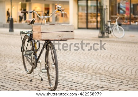 A retro style bicycle with a wooden basket, is parked on a cobblestone street.