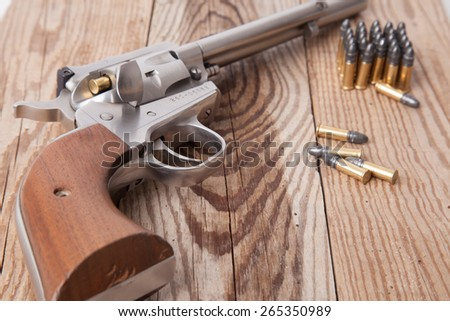 A revolver on a piece of wood. - stock photo
