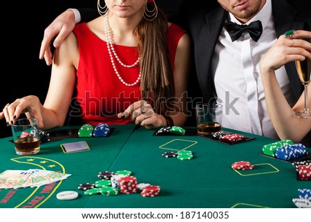 A rich elegant couple gambling in a casino - stock photo