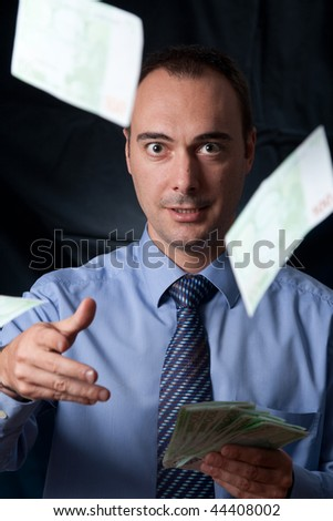A rich man is throwing away a wad of money. Interesting framing and look of his eyes. Conceptual image for wealthy lifestyle, success, spending money, and so on. - stock photo