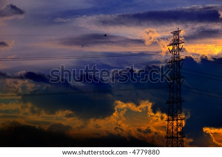 A rich sunset of golds, oranges and blues is the backdrop for this silouetted transmission tower. - stock photo