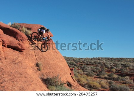 A rider drops down a steep sandstone feature in the Utah desert.