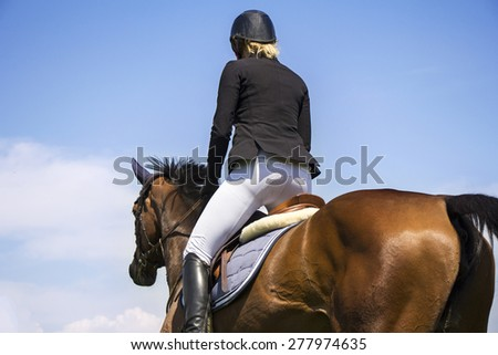A rider on horseback competing in equestrian tournament - stock photo