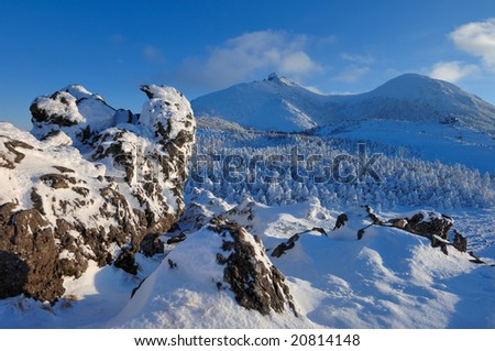 A ridgeline of the evening and a rock and the rime on trees - stock photo