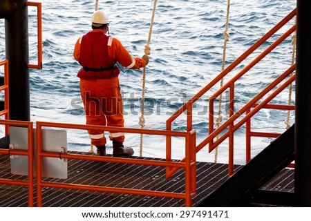 A rig worker holding a swing rope while waiting for a vessel in order to be transported to a nearby rig - stock photo