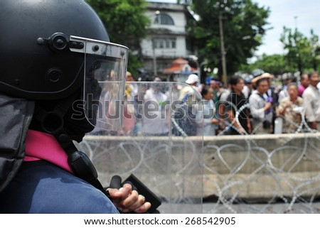 A Riot Police Officer Stands Guard During a Political Protest - stock photo