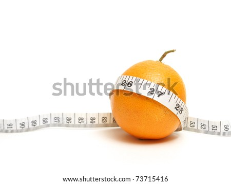 A ripe citrus fruit with a measuring tape to represent a fit waistline from healthy eating. - stock photo