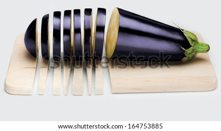 A ripe eggplant on a cutting board both partially sliced. - stock photo