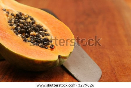 A ripe papaya showing its seeds on a wooden choping block. - stock photo