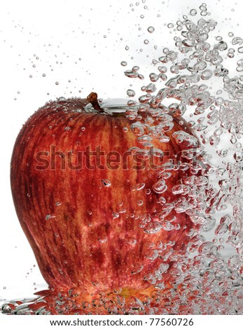 A ripe, red delicious apple with rising water bubbles. - stock photo
