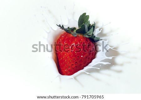 A ripe red strawberry is dropped into milk and makes a nice splash.