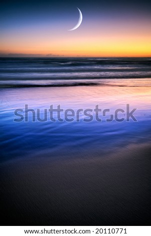 A rising moon on a calm ocean with blue sand dunes and a colorful sunset
