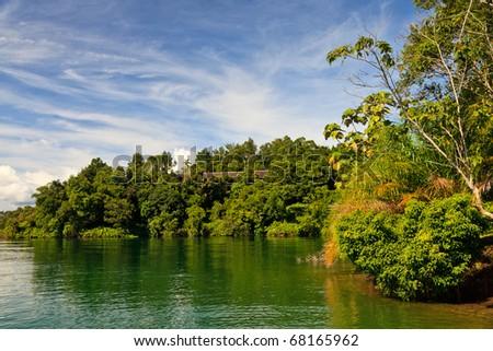 A river flowing through a  tropical rainforest - stock photo