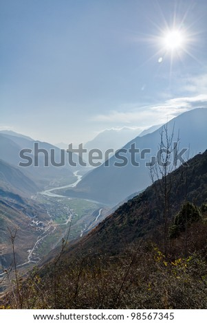 A river lighted by the sun between mountains - stock photo