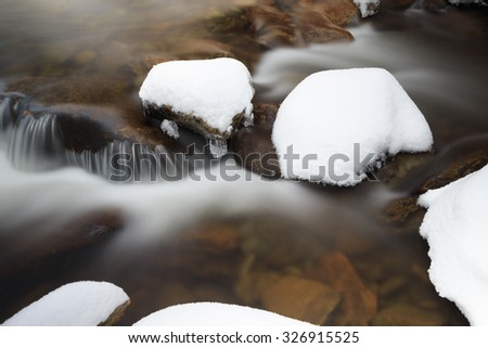 a river with rocks in snow and icicles, russian nature - stock photo