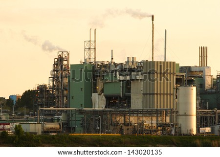A riverside chemical factory at sunset with a clear sky.