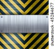 A riveted brushed aluminum plate on a construction hazard stripes background with carbon fiber inlay. - stock photo