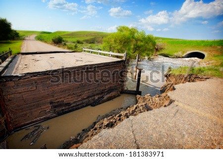 A road and bridge damaged by muddy, flood waters. - stock photo