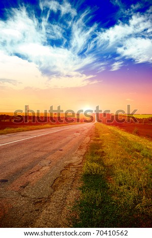 a road at the evening in the field - stock photo