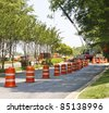 A road construction project with orange and white barrels - stock photo