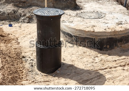 A road construction site covered in sand with a sewer hole - stock photo