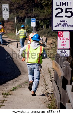 A road crew worker running to catch up with the paver. - stock photo