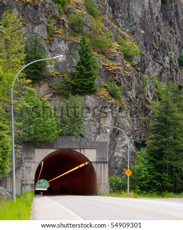 A road going to tunnel daytime. - stock photo